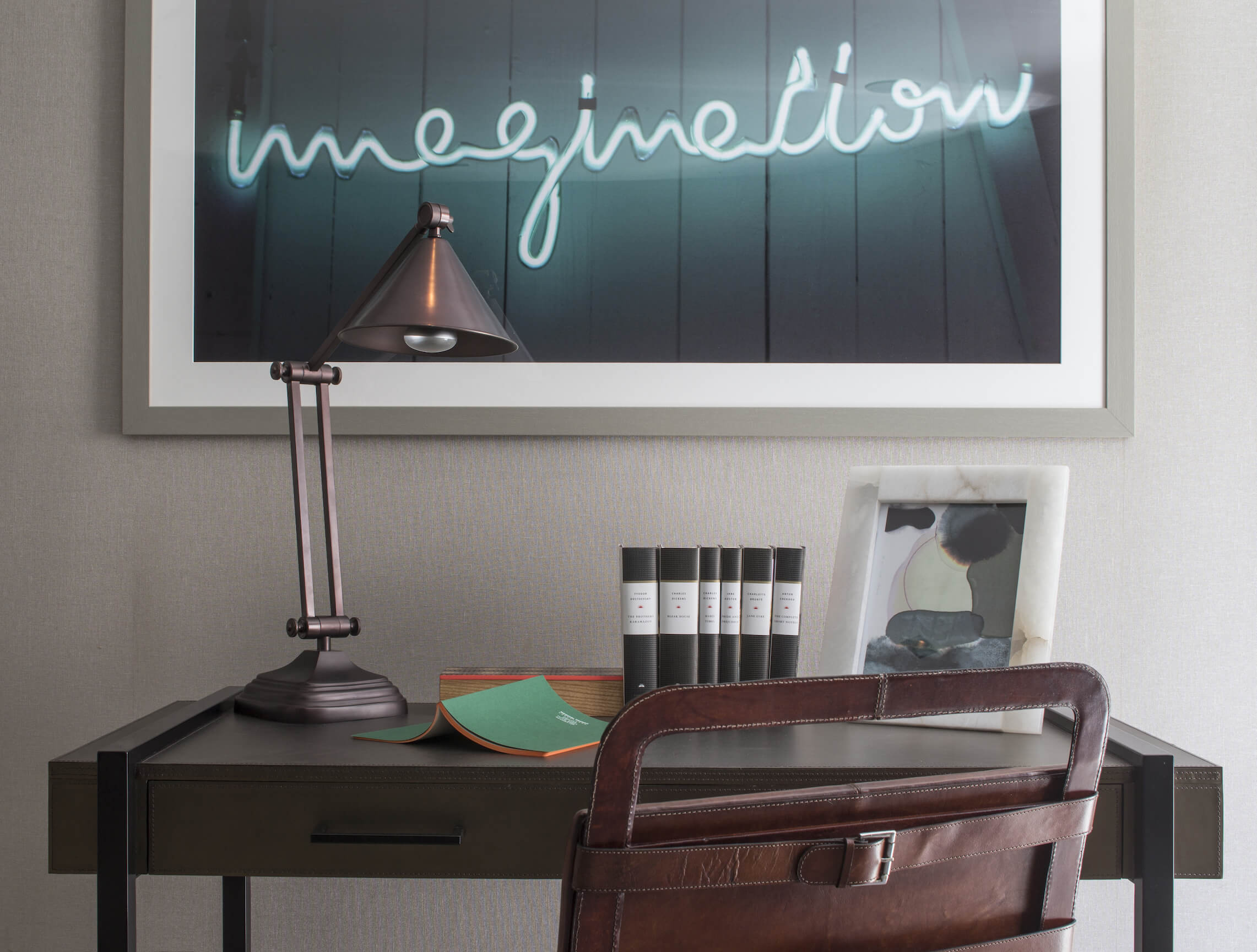 """Above the sleekly minimalist desk hangs a neon """"imagination"""" art piece, adding a splash of glowing color to the space."""