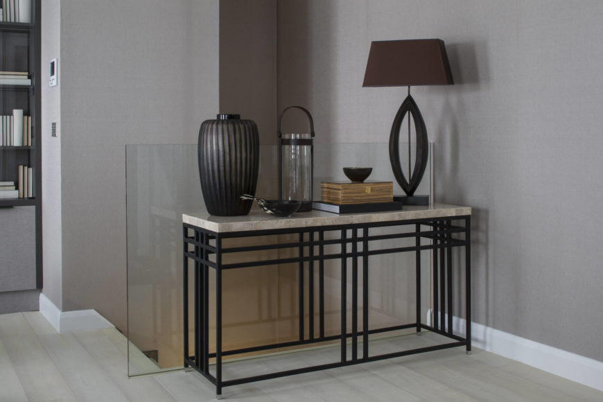 The main staircase is defined by seamless glass wall, with this marble topped, black metal frame table holding a lamp and decorative elements.