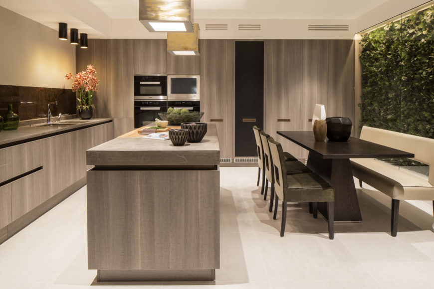 The large island features a single segment of natural wood countertop at center. Countertops all feature a recessed dividing strip, with a copper toned backsplash running the wall length at left. Dining table in dark wood features an array of leather bound chairs paired with a light beige bench.