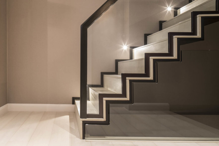 The glass framing the staircase is cut to exacting shapes, mirroring the steps themselves above and below.