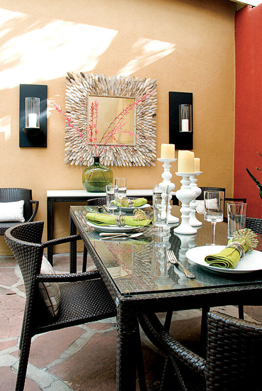 This patio dining space mimics a traditional indoor space, replete with sconces on the stucco wall, flanking a large decorative mirror. Resin wicker seating and glass topped table complete the dining set.