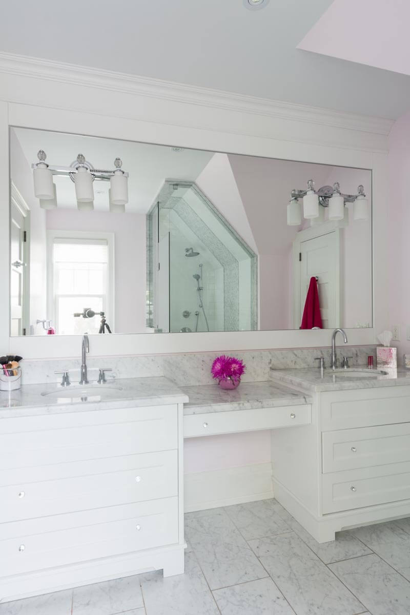 Bright primary bath features marble countertops matching the tile flooring, with white dual vanity standing beneath an immense mirror.
