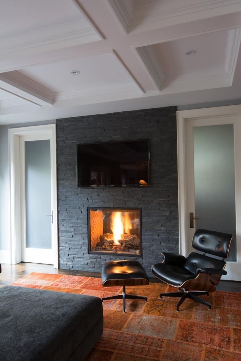 Two rooms are connected via this pass-through fireplace resting in a slate brick wall, flanked by fogged glass doors. A contemporary black leather, wood frame chair sits on a burnt orange rug beneath an elaborate, detailed ceiling design.