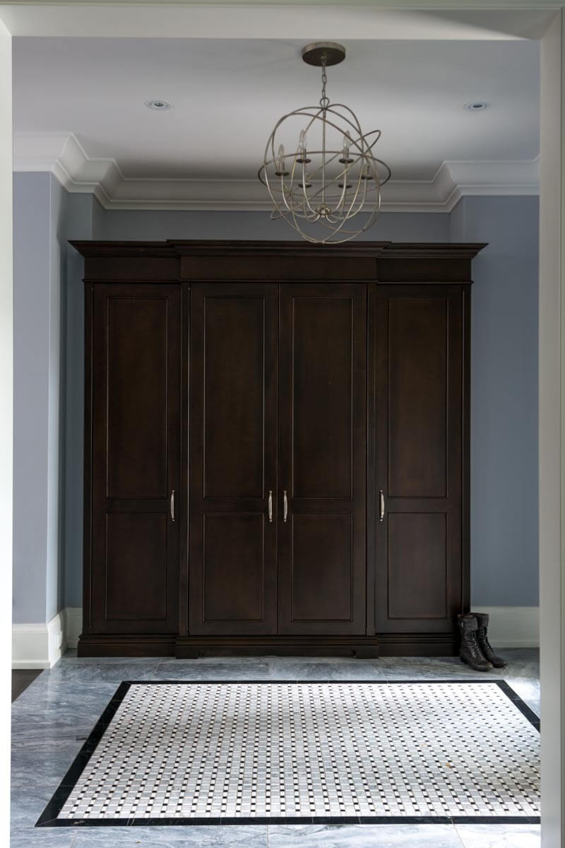 Marble flooring in this hall stands below a full height rich wood cabinet, with a second spherical chandelier matching the one on top of the staircase.