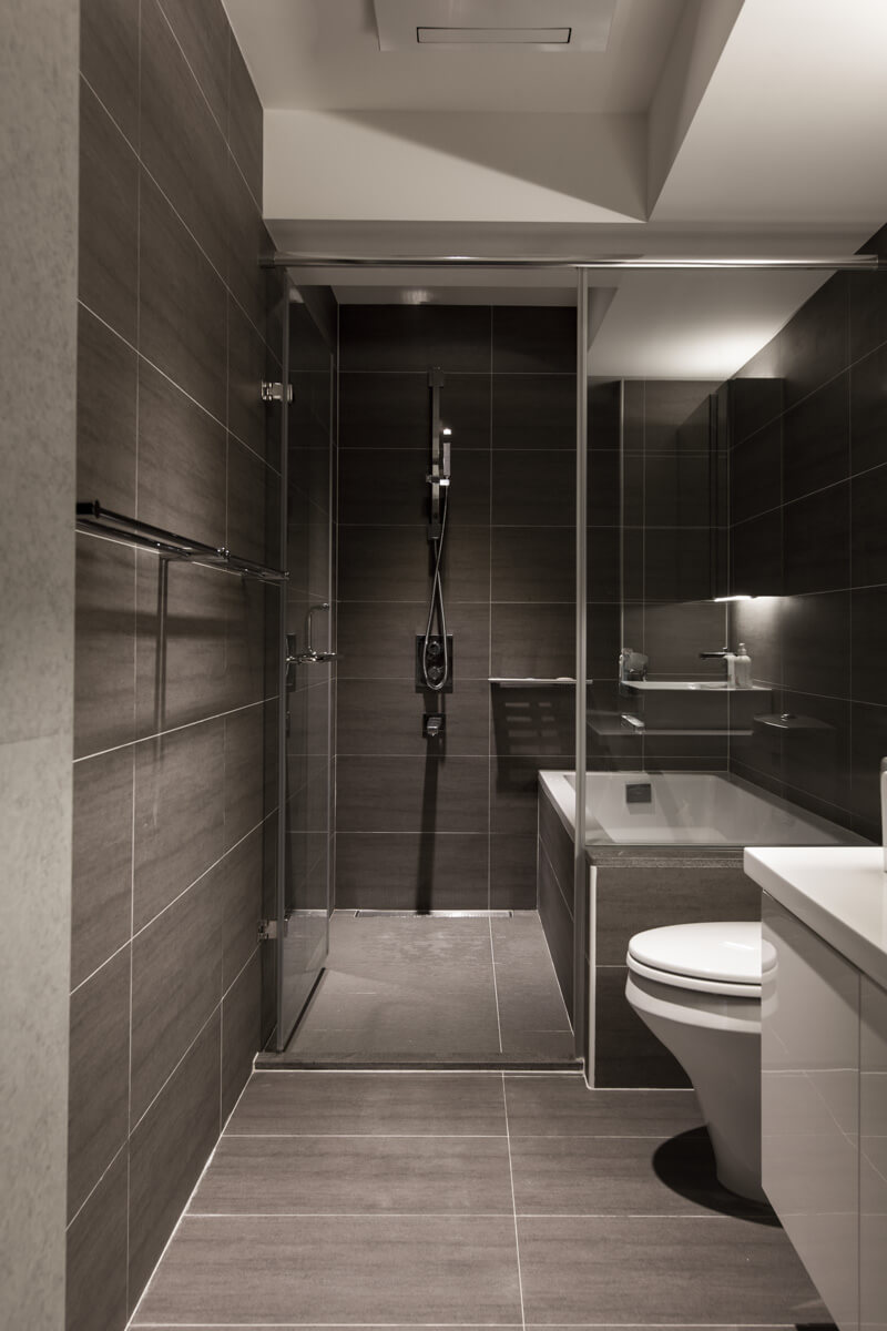 The gray tile bathroom has the shower and bathtub enclosed in glass.