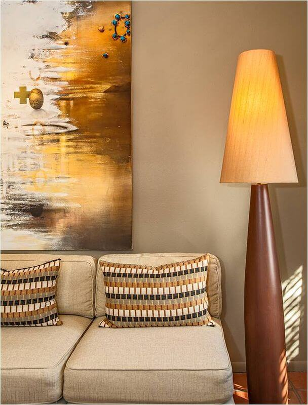 Contemporary natural wood floor lamp stands next to the sectional and an abstract painting in the living room.