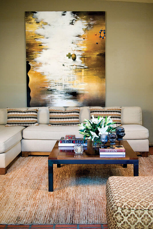 Viewing inside the home, we see an elegant contemporary L-shaped sectional hugging a natural wood and black metal frame coffee table over a burnt beige rug and red brick tile flooring.