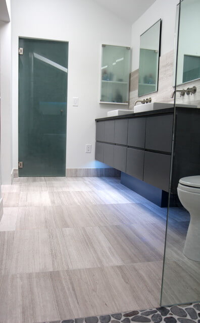 From the shower door we see the change to gray floors with a wood grain pattern, the black vanity with LED lighting beneath and dual vessel sinks.