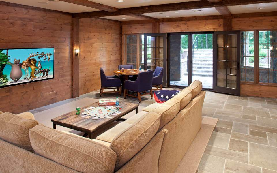 Lower level family room features a variety of color, including beige L-shaped sectional and a quartet of plush violet chairs around a circular wood dining table. Double patio doors lead to stairs opening toward the expansive back yard.