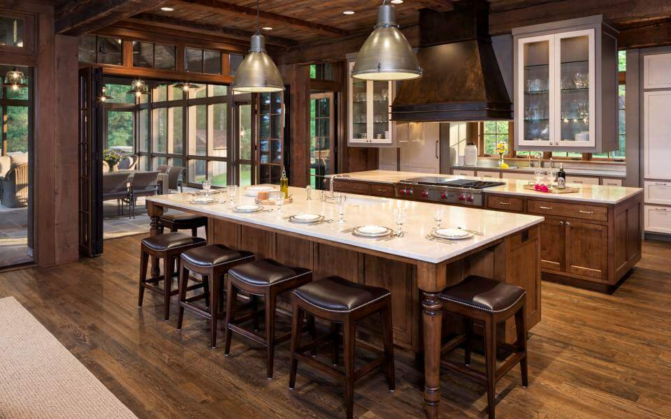 The kitchen centers around two lengthy islands: a serving one, with bar style seating in foreground, and one containing the range and oven, with overhead glass door cabinetry, in background.