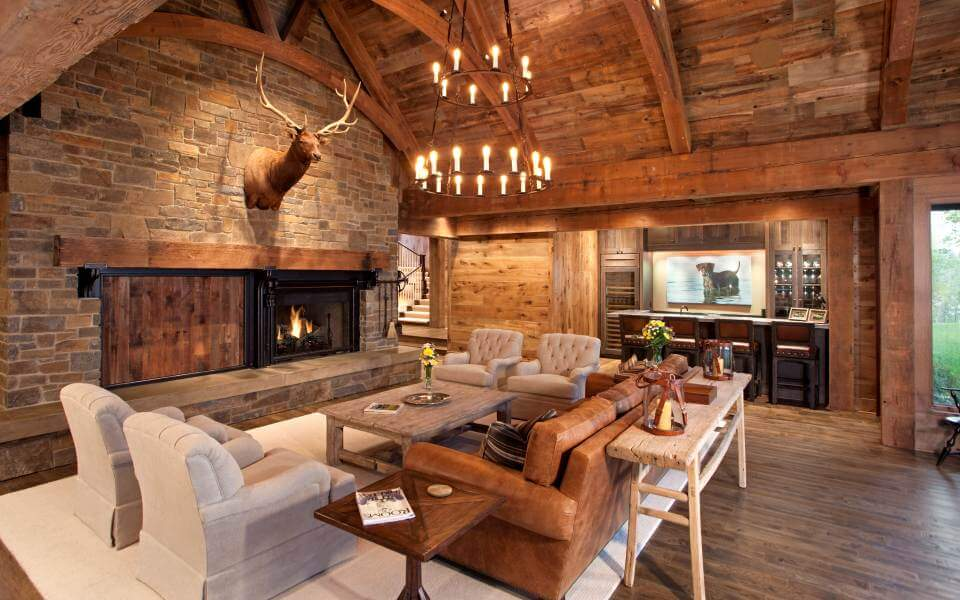 From the opposite view, we see the massive stone fireplace wall at left, with the surrounding furniture arrayed on a white area rug over the hardwood flooring. Full bar space appears at right.