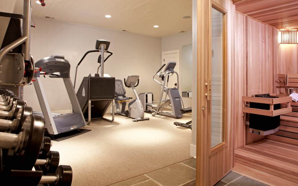 Just outside of the sauna, we see a full exercise room, replete with a spectrum of free weights and machinery.