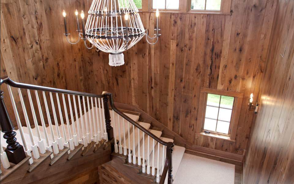 The central grand staircase rolls white carpeting down natural wood steps, wrapping around a central void. White and metal chandelier hangs above at center.