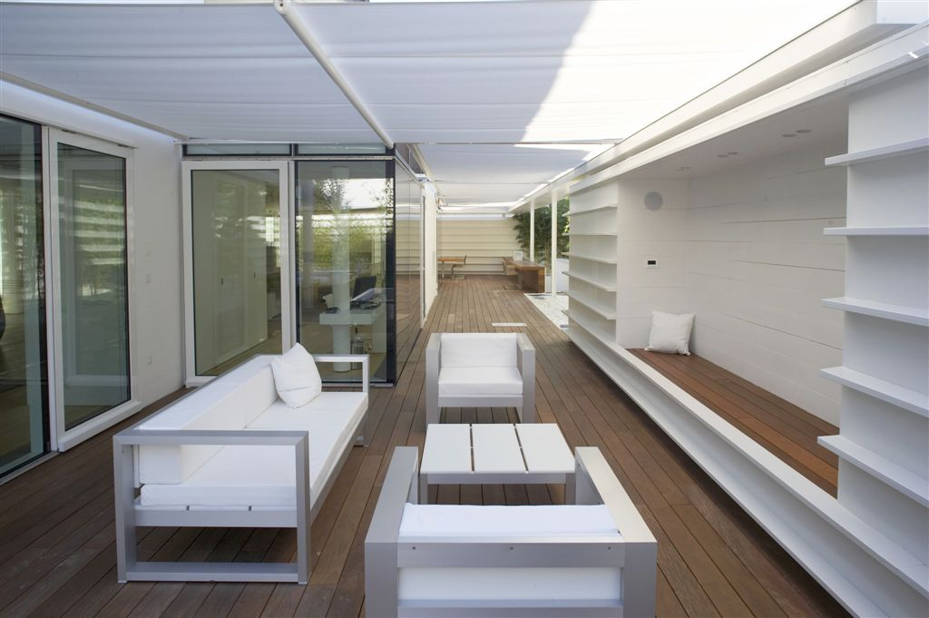 Large deck with a patio area featuring white furniture set.