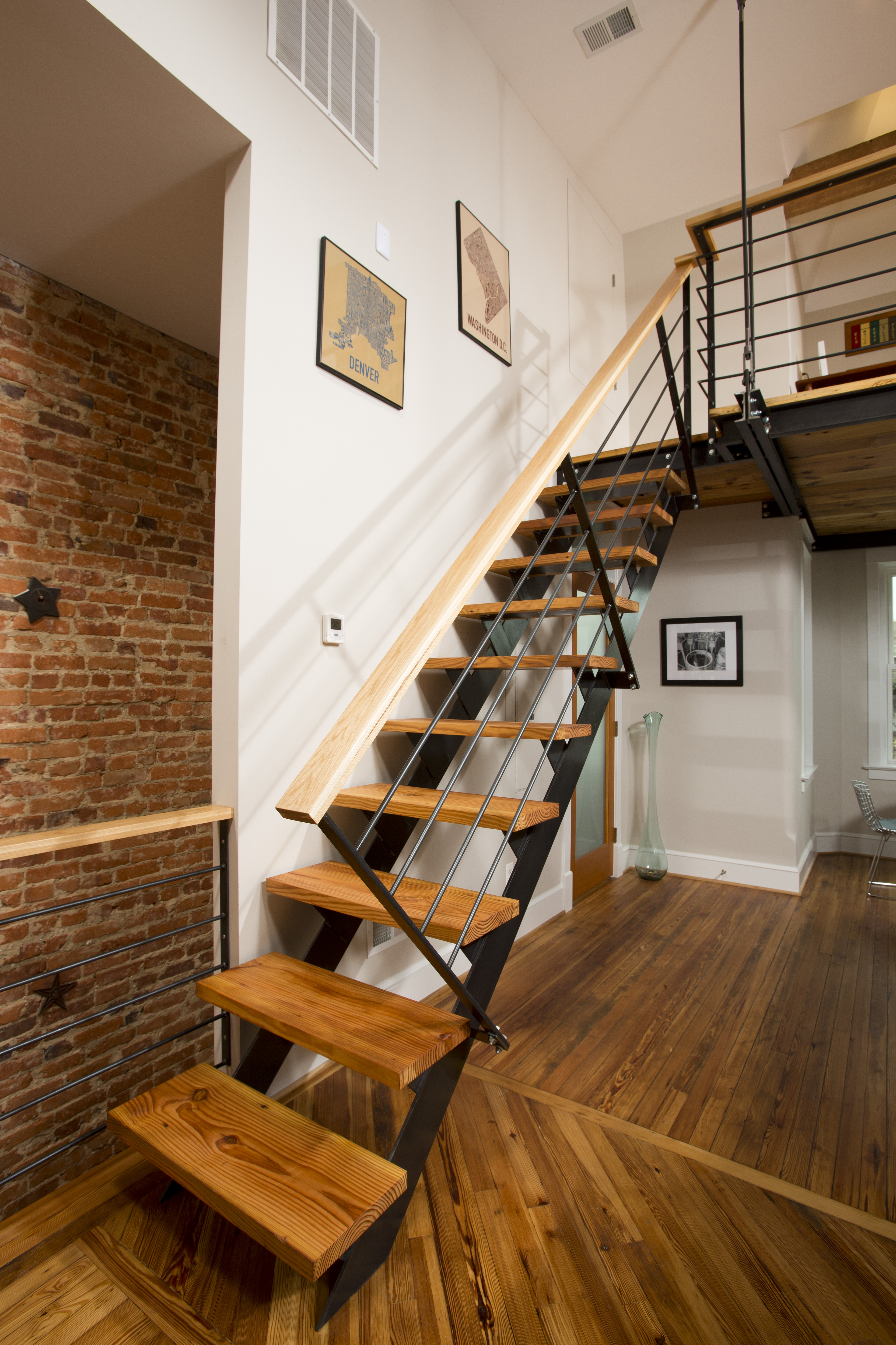 The frame of the open staircase going up to the loft keeps the space feeling open. Pine footrests match the wood throughout the condo.