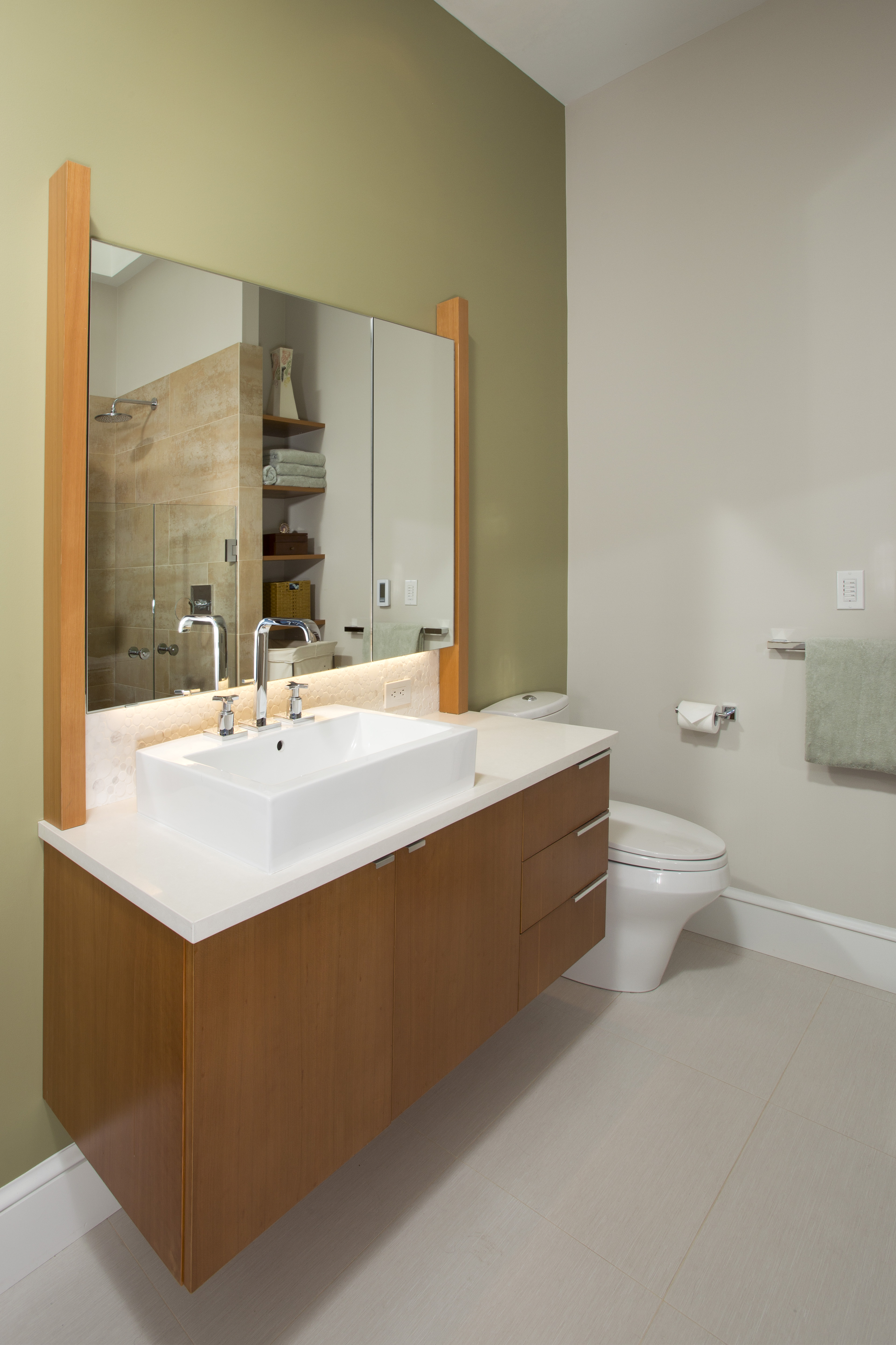 The other bathroom has a natural wood vanity with minimalist drawer pulls. A large white vessel sink melds into the countertops.