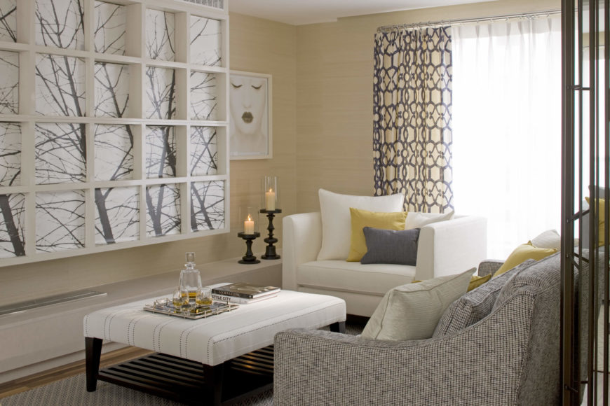 To the right, we see a subtly textured sofa paired with an extra wide, white chair and white ottoman coffee table, standing next to a white grid-design art piece on the wall. Soft cream color contrasts with the hardwood flooring and bold white furniture.