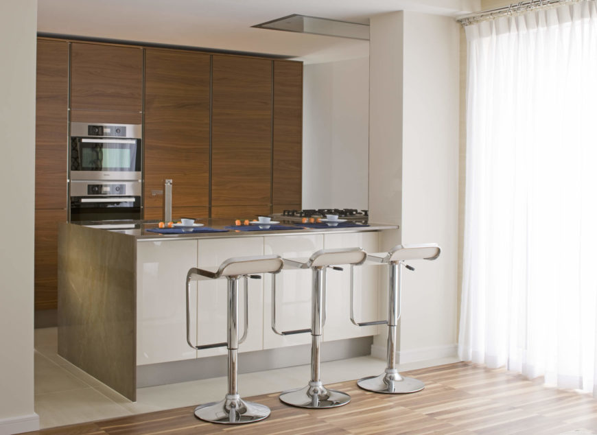 The cozy kitchen sits off to the side, subtly distinguished by its mixture of metallic and glossy white textures, as well as floor to ceiling natural wood paneling. The marble countertop, along with a trio of chrome bar stools, allows for informal dining.