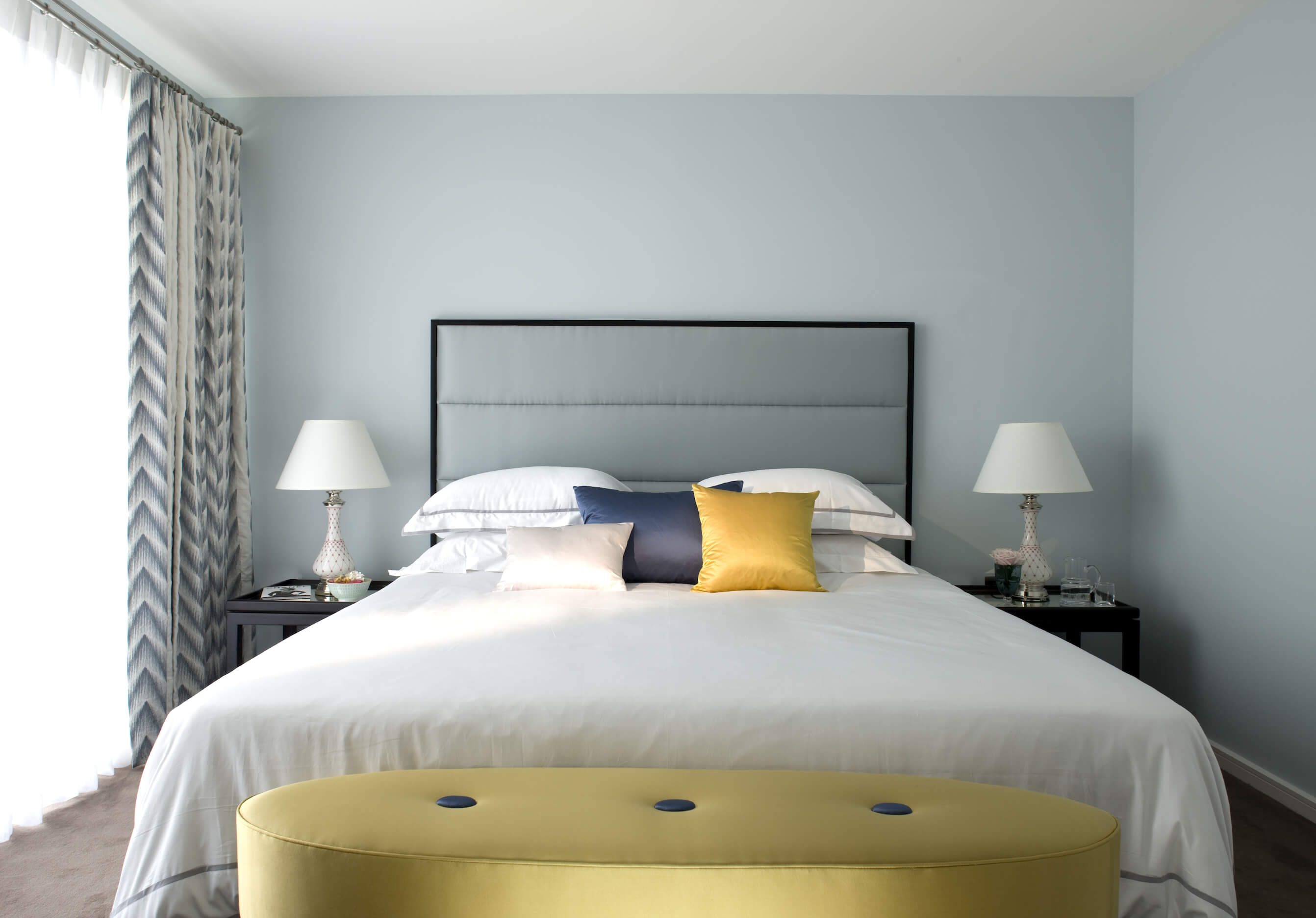 In the bedroom the gold accents on white are joined by bold blue tones, as seen on the pillows and oval ottoman at the foot of the bed. Soft sky blue walls brighten the space.