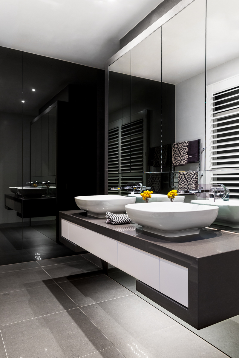 Bathroom features a floating dual vanity in dark and white tones, with a pair of vessel sinks standing in contrast with glossy black walls and grey tile flooring.