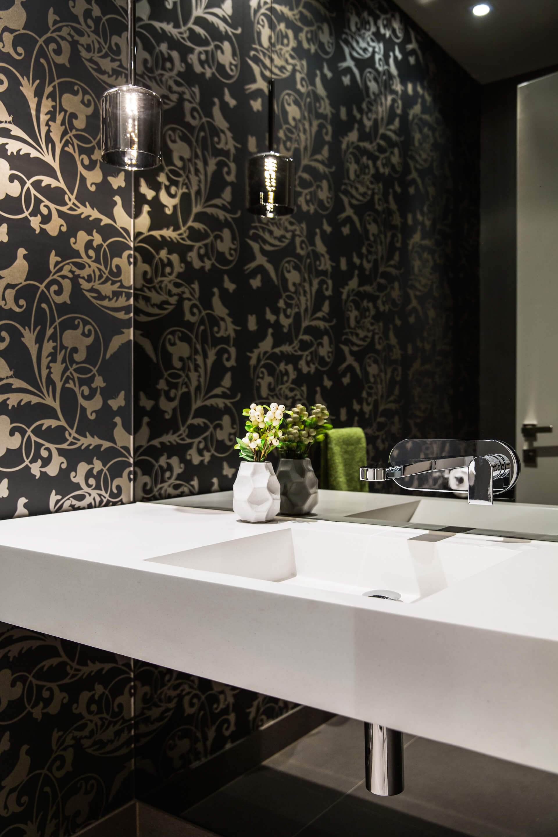 Powder room features a singular white floating vanity with modern chrome tap built into the mirror. Gold patterned dark walls pair with the reflective drum lighting.