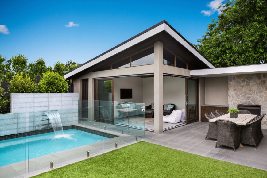 Across the back yard we see the glass wrapped pool abutting the pool house. Featuring a small living room with sliding glass panels to openly share space with the patio, the pool house also boasts a full, discrete bathroom facility.