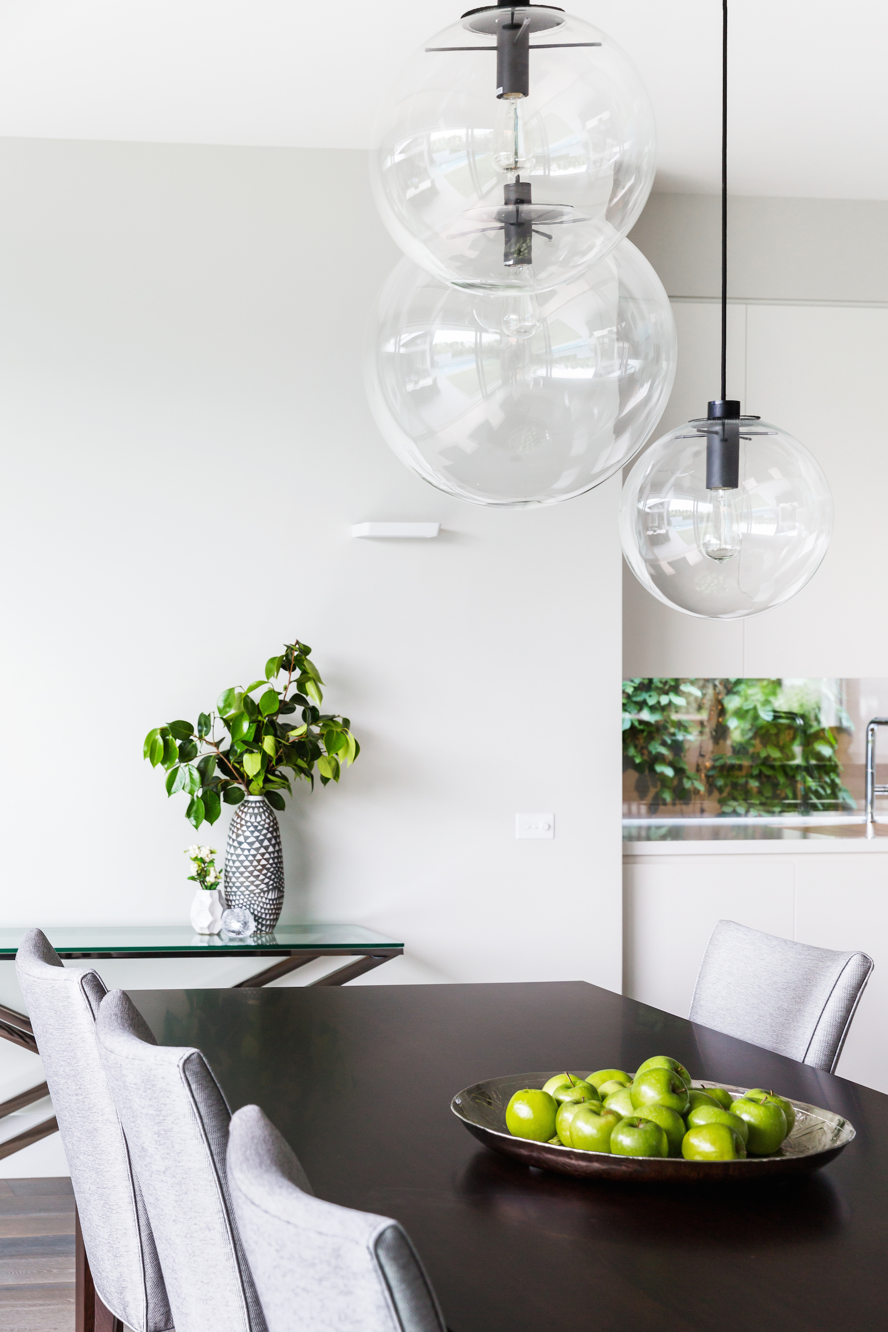 The dining table is a lengthy, dark stained hardwood piece, flanked by bespoke grey parson chairs. A set of spherical pendant lights float above.