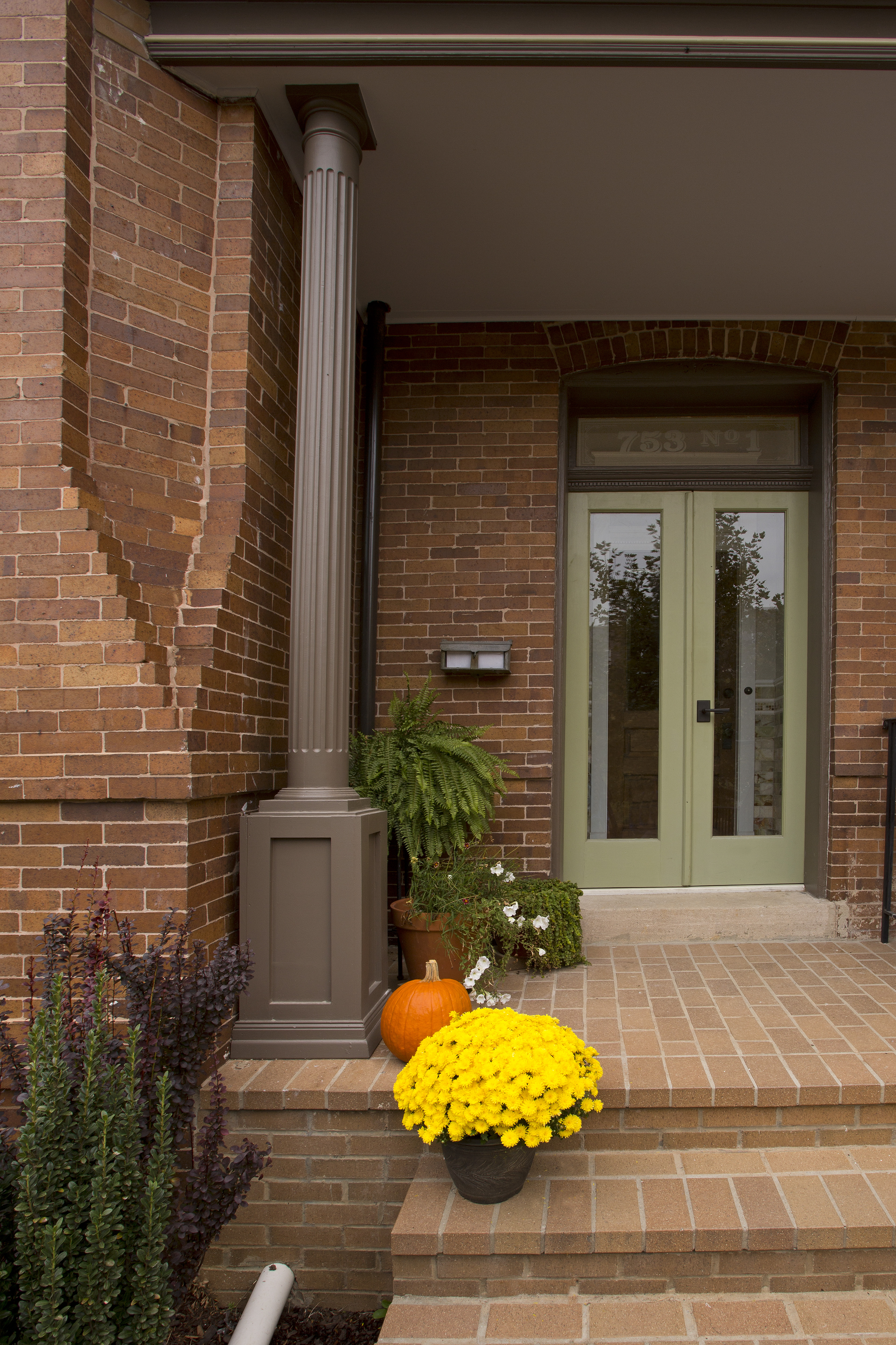 The warm stone steps up to the condos are decorated with bright fall flowers and other plants.