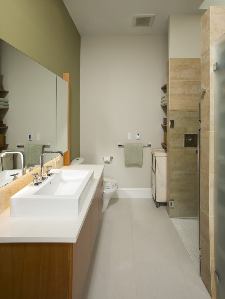 A long view of the bathroom shows a small built-in shelving unit with a laundry hamper beneath it to one side of the shower stall.