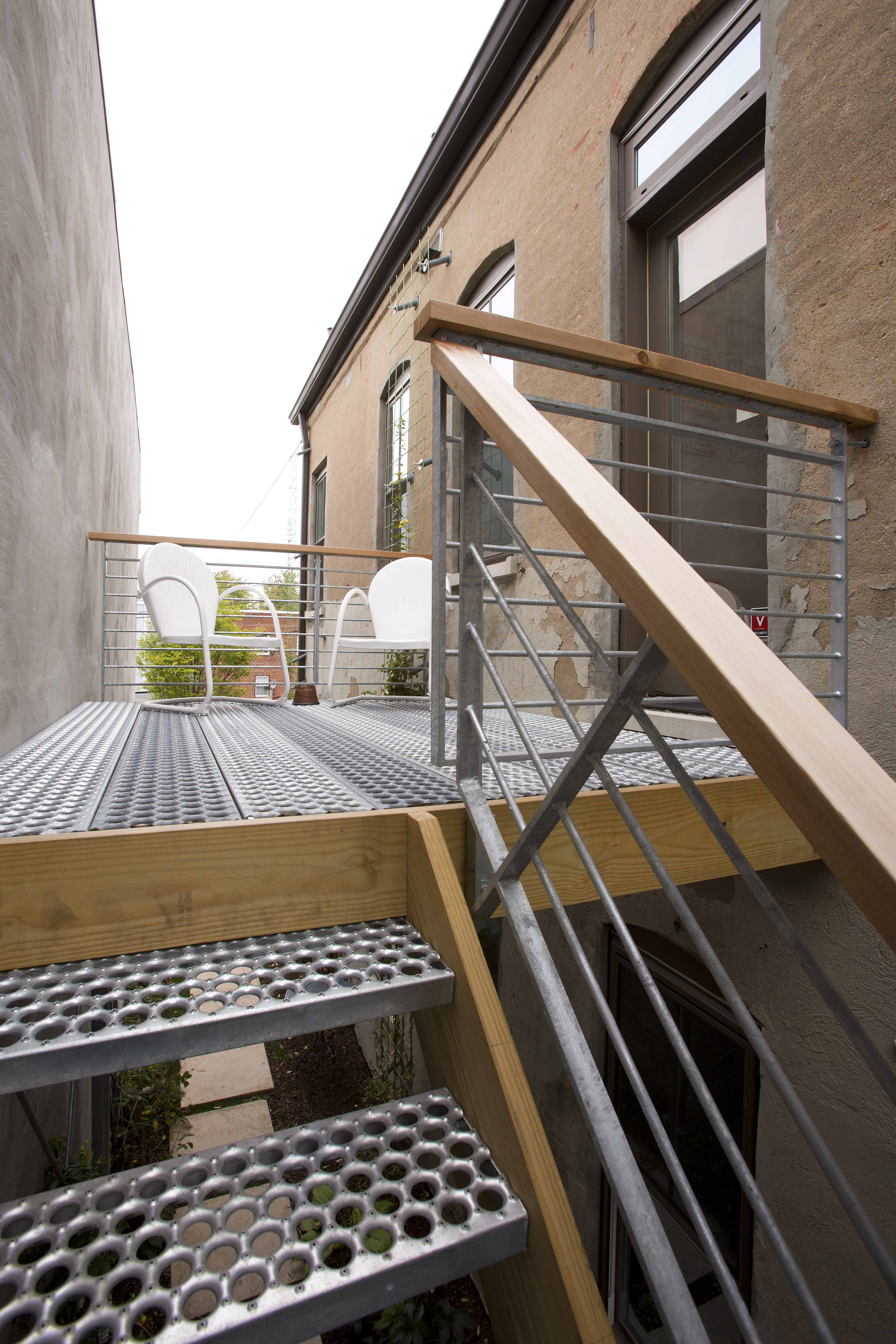 A landing coming off the back of the unit employs industrial-style stairs down to a garden walkway to the backyard.