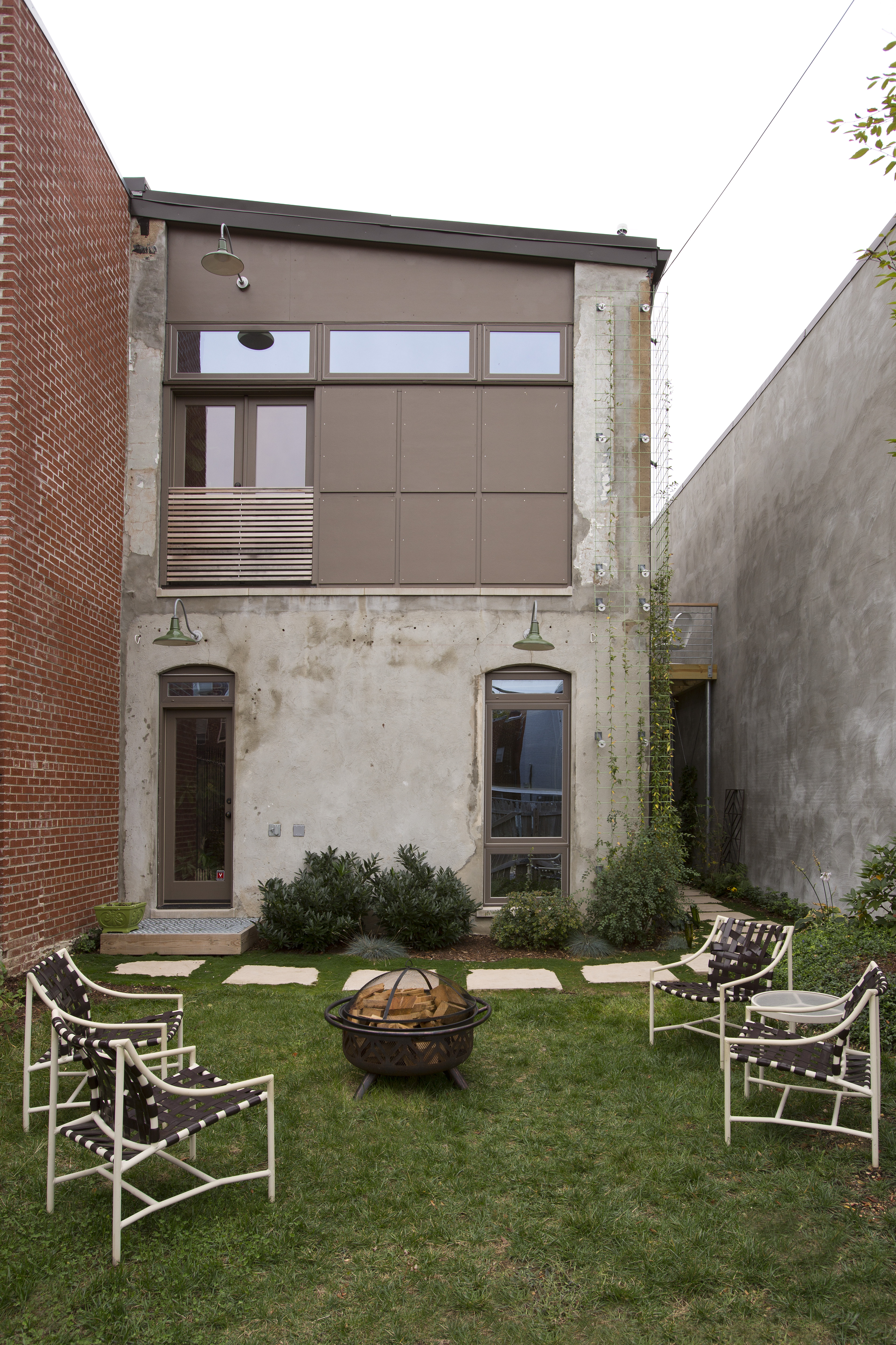 The small backyard has a metal firepit and several lawn chairs. The stone path leads around the back to another door. The outside of the building is concrete.