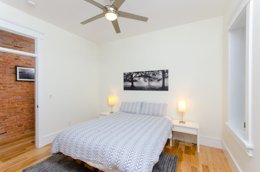 The second bedroom is minimalist in design, with sleek white night stands. The all white room makes the blue bedding and rug the focal point of the room.