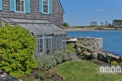 An outside view of the greenhouse and the sea wall. The wall has a ladder to go down to the shore.
