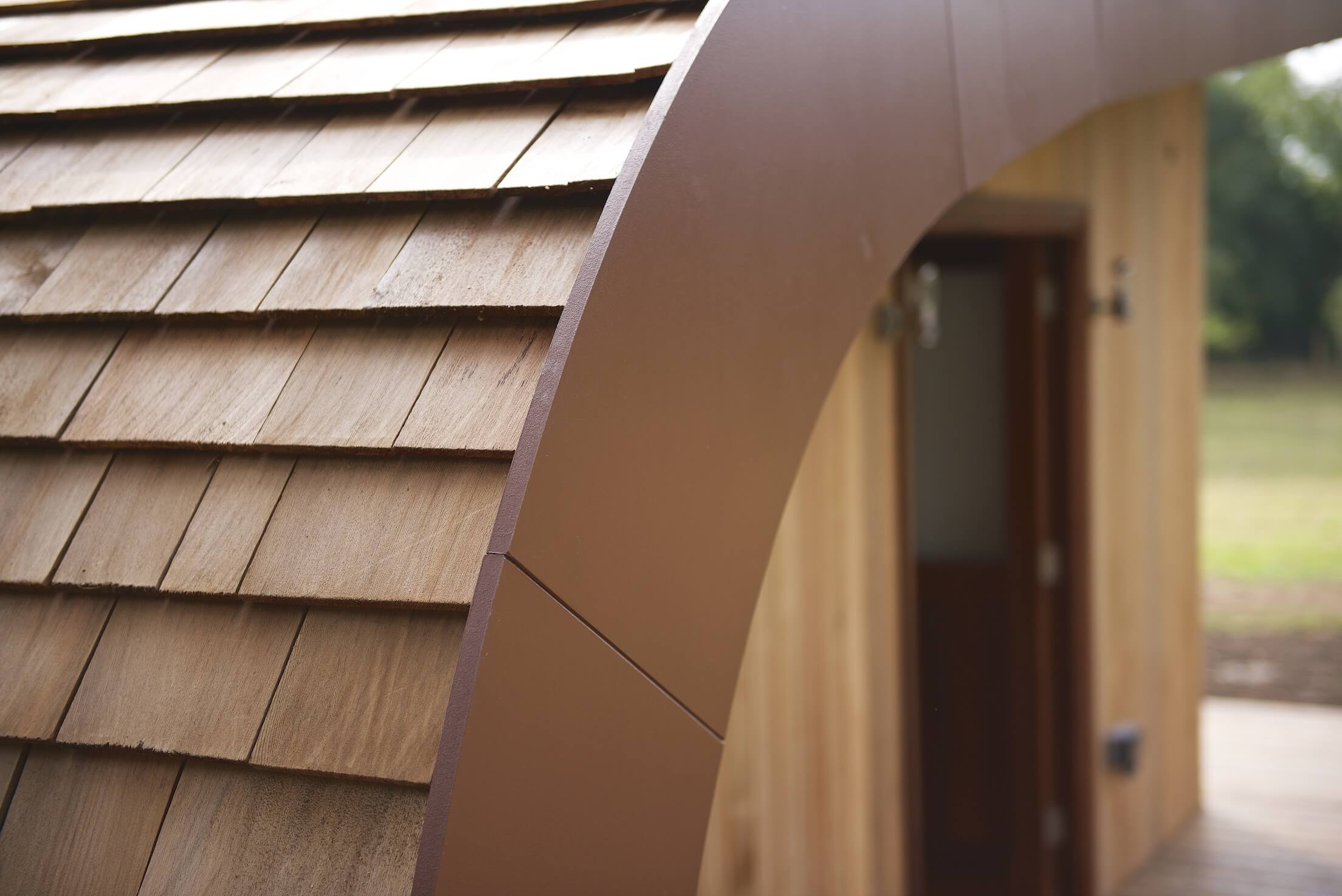 Close view of the cedar shingles forming the curved portion of the roof.