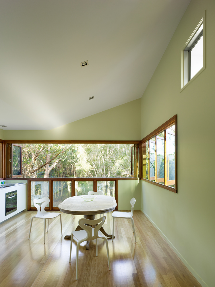 The upper level dining space holds a set of retractible, louvered windows, allowing the area to open freely to the elements. Natural hardwood flooring contrasts with lightly colored walls.