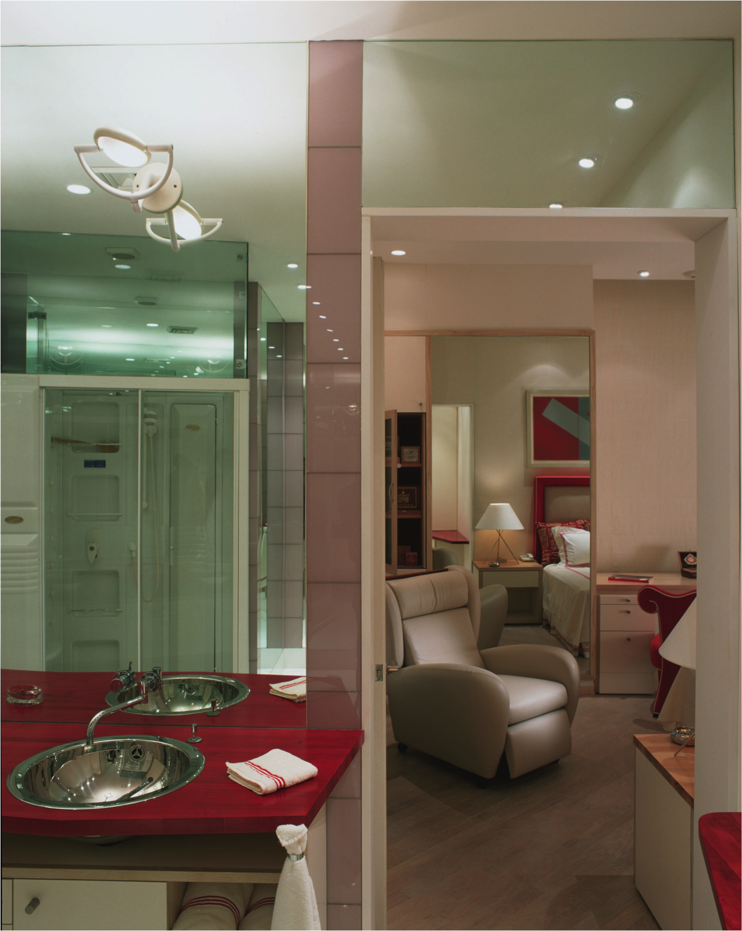 Taken from the doorway between the primary bedroom and the primary bathroom, this photo shows the bright red accents of the primary bedroom filtering into the deep red butcher block countertops of the bathroom vanity. Reflected in the mirror is the whirlpool spa shower stall.
