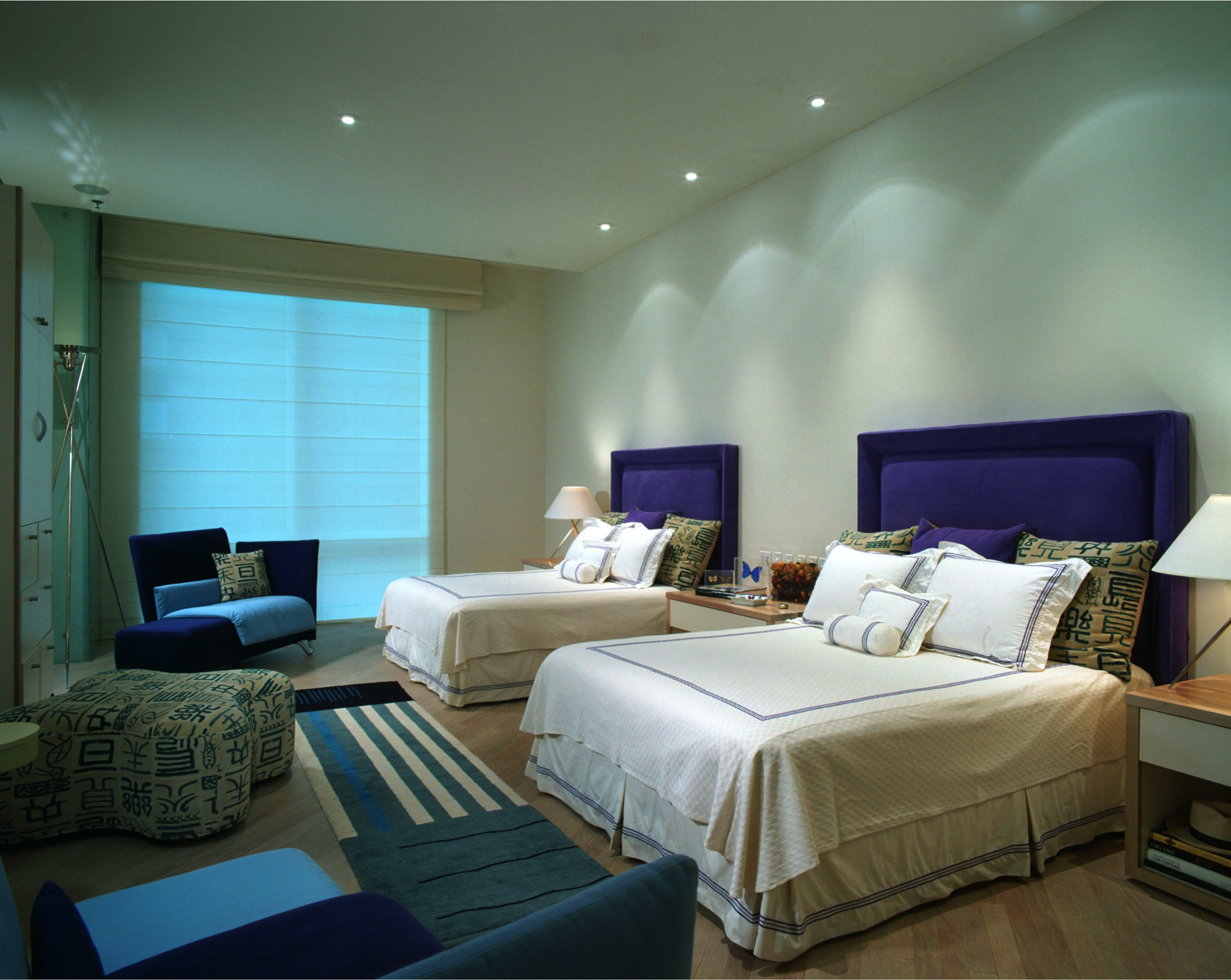 The guest bedroom has two queen beds with matching royal purple headboards. A long runner connects the two seating arrangements at either end of the room.