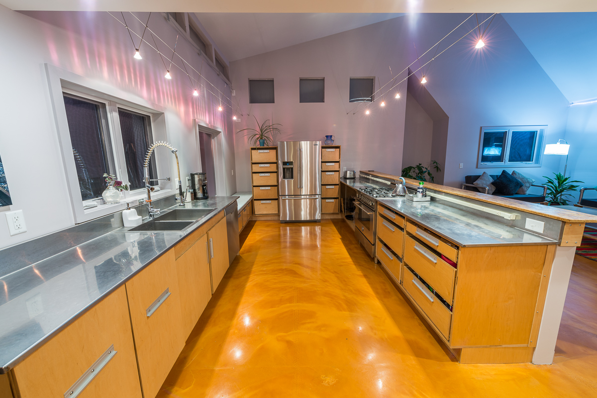 Two sets of rail lighting are suspended from the walls and ceiling above the kitchen countertops. The stainless steel countertops and fixtures line both sides of this wide galley kitchen.