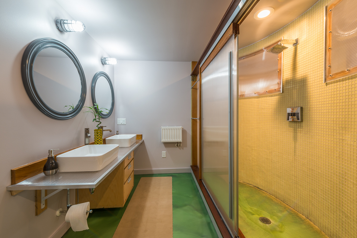 The primary bathroom has a shower stall with ample room, and dual sinks. Stainless steel countertops make another appearance.