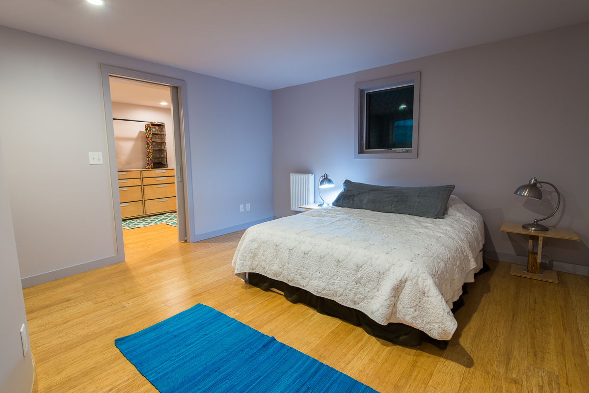 Dove gray walls continue into the primary bedroom, with simple modern lamps on nightstands very similar in style to the dining table. Through the doorway is a massive walk-in closet.