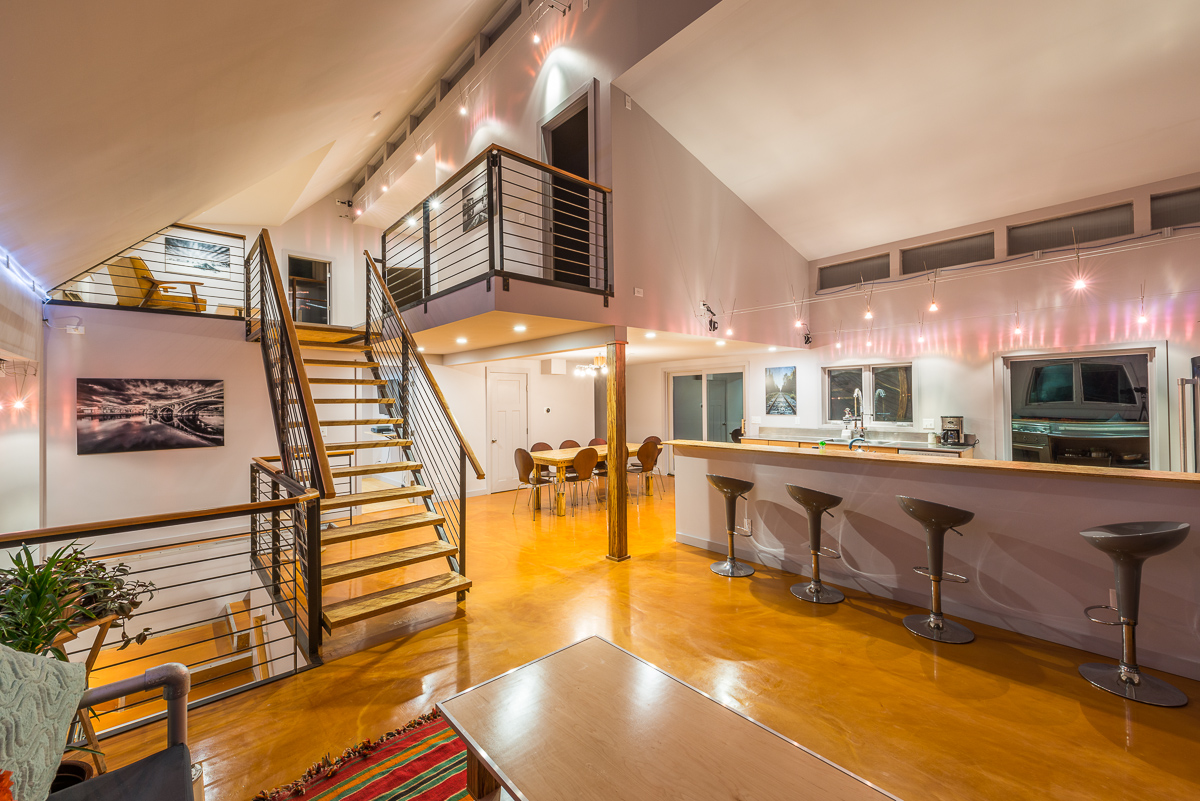 Upon entering the home, the main living area, including the kitchen, living room and dining room is clearly visible, as are the stairs to the upper and lower levels. Industrial materials are evident in the couch and in the rail lighting.