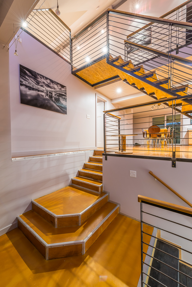 The staircase leading down to the lower level moves from thick platforms to a staircase more similar to the one leading upstairs.