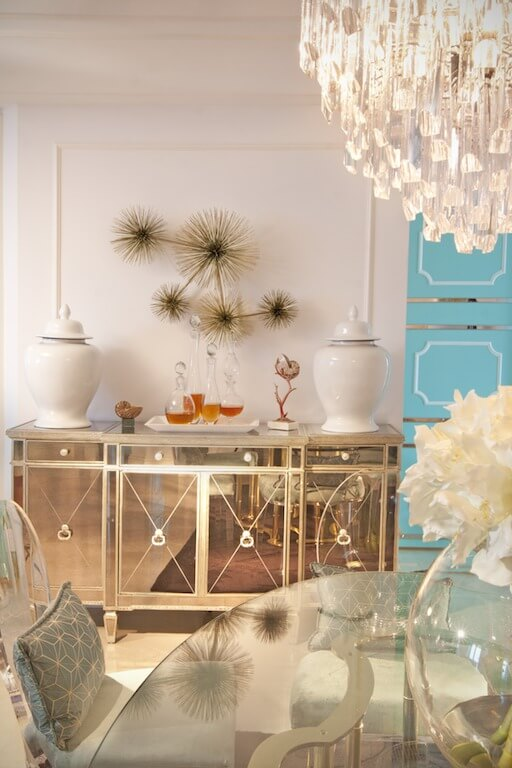 The reflective buffet to one side of the glass dining table is topped with glass decanters and a modern wall sculpture.