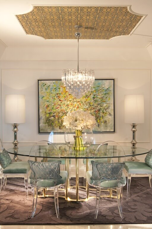 The transparent oval-backed dining chairs are softened with plush Tiffany blue cushions and pillows. A large piece of art hangs on the wall behind the dining table. An elegant crystal chandelier and two floor lamps light the area.