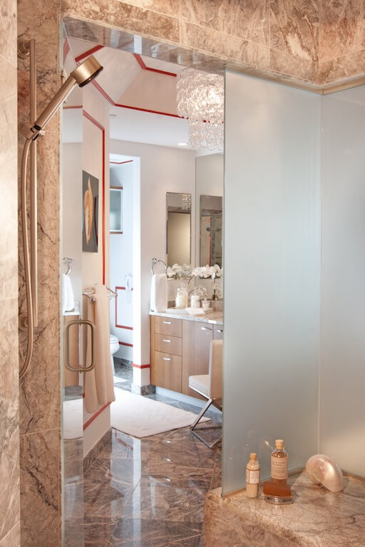 The warm marble bathroom has red piping along the walls and fixtures. A chandelier hangs above the natural wood vanity.