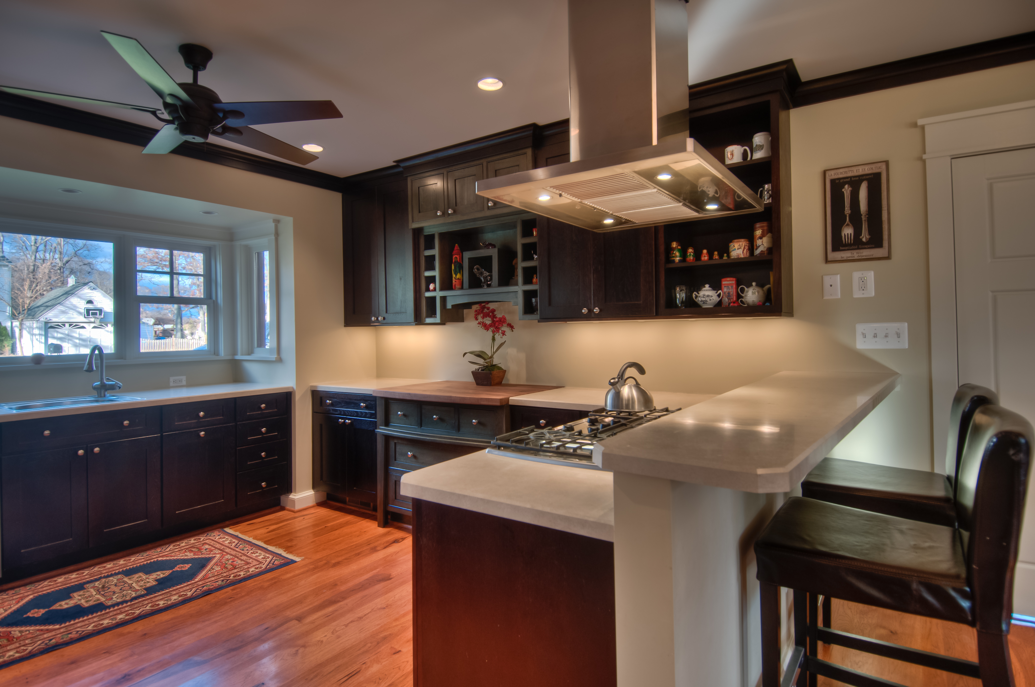 Another view of the kitchen, showcasing the raised bar with seating for two, the warm hardwood floors and small rug in front of the sink. A ceiling fan helps keep the kitchen cool.