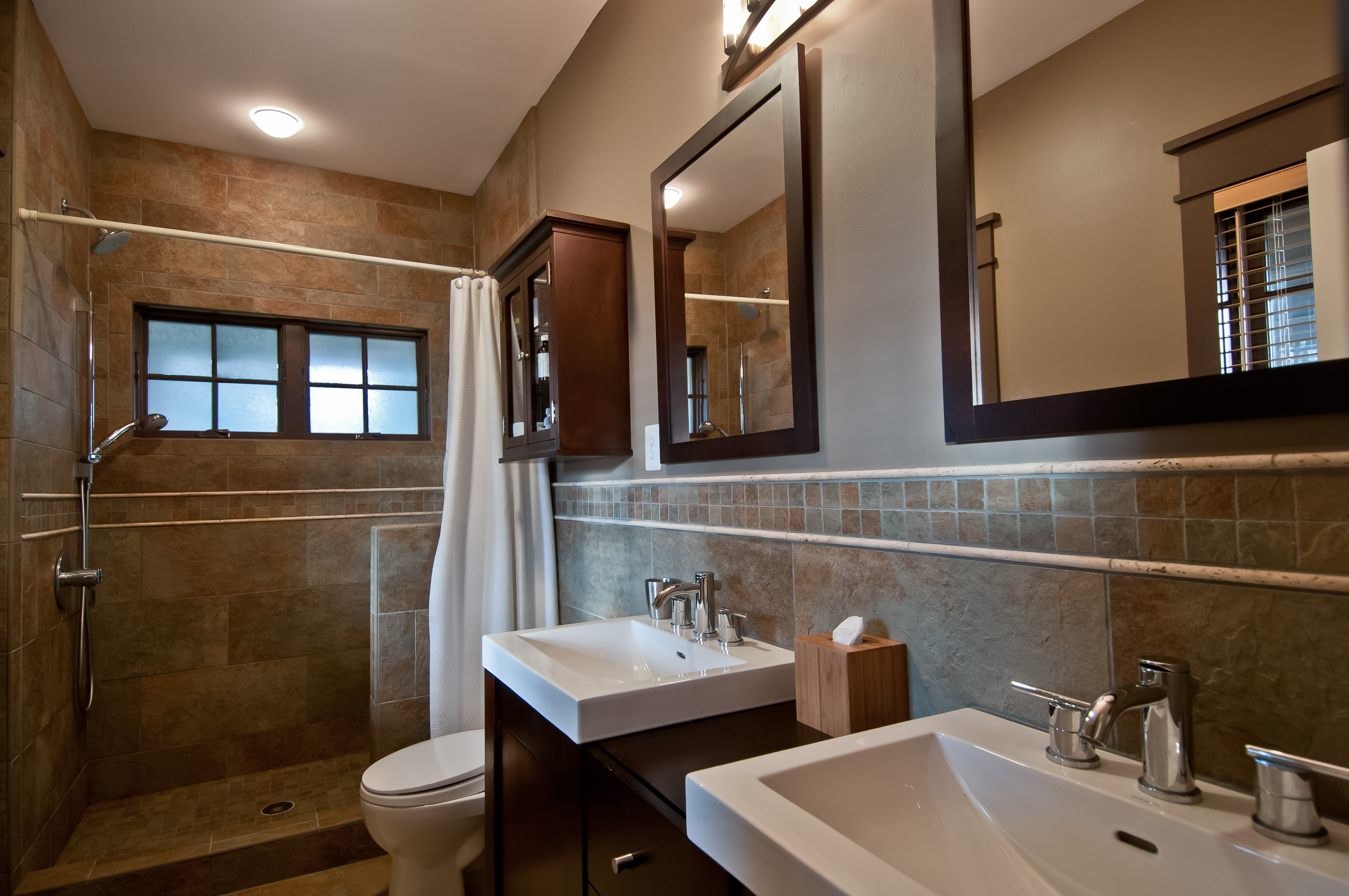 The stone and tile primary bathroom has beautiful natural cherry cabinets and an unenclosed shower stall. Chrome fixtures and dual mirrors above the his-and-hers sinks complement the matching medicine cabinet.
