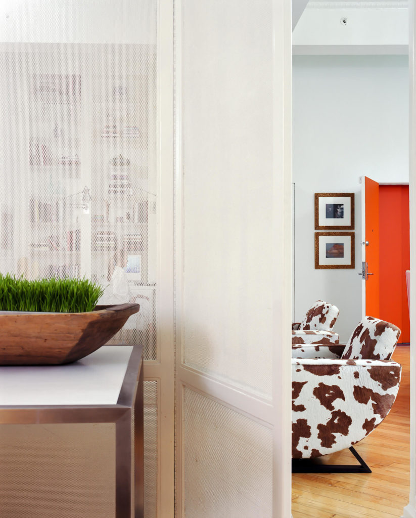 Through a porous white dividing wall we see the open living room and full height shelving, with cow print chairs and bright orange entryway at right.