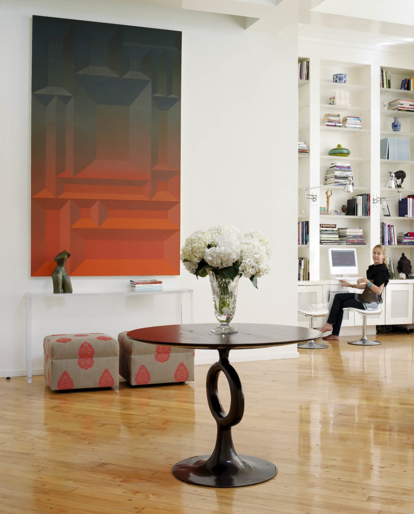 At the opposite end of the central open space, we see a singular dark carved wood table, all-glass wall table over a pair of patterned ottomans, and massive colorful art piece standing in contrast to the white walls and hardwood floor. White built-in shelving and desk is seen at right.
