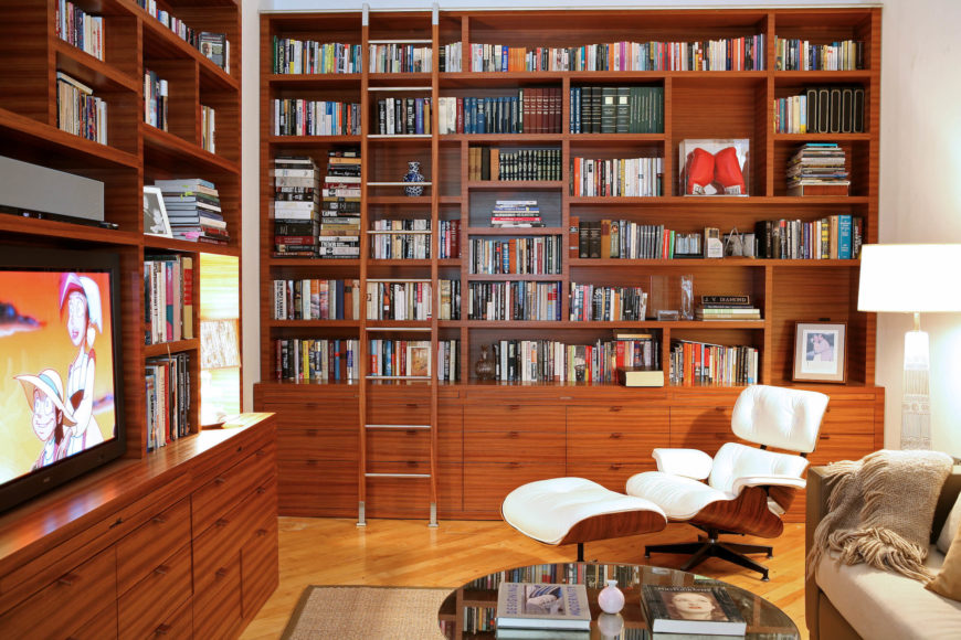 In the office area, we see a large expanse of natural wood bookcases on two walls, surrounding a beige sofa, mirrored coffee table, and carved wood frame, white button tufted easy chair and ottoman.